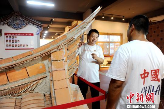 陈荣文(左)向学徒讲解闽南传统民居营造技艺。 张金川 摄